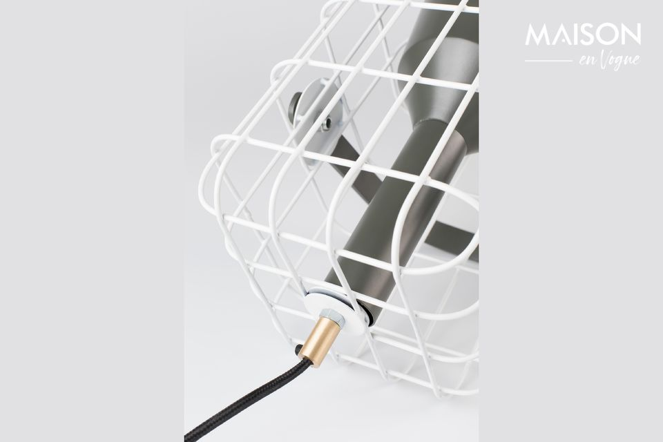 The lamp is surrounded by a white cage in lacquered iron that is pleasant to look at
