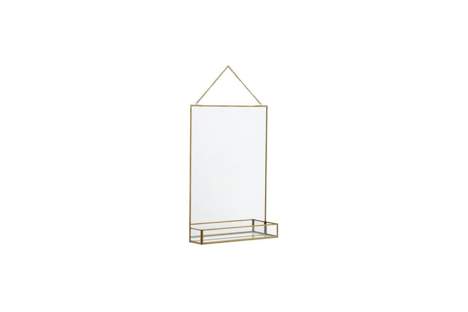 A mirror and its shelf highlighted by a gold finish