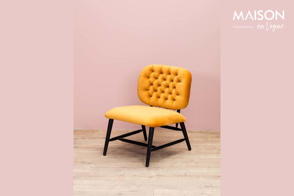 A velvet-like armchair with an ochre-coloured, upholstered backrest